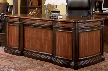 Executive desk finished in cherry and black with seven drawers.